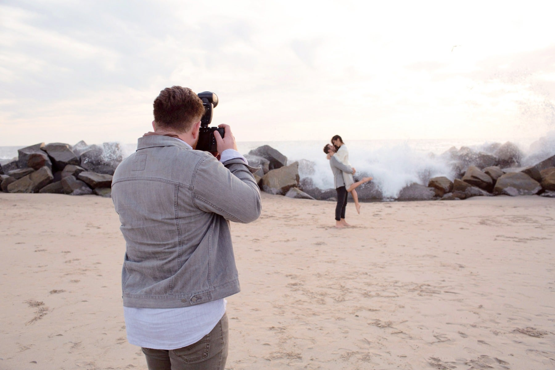 Photographer at beach with wedding couple