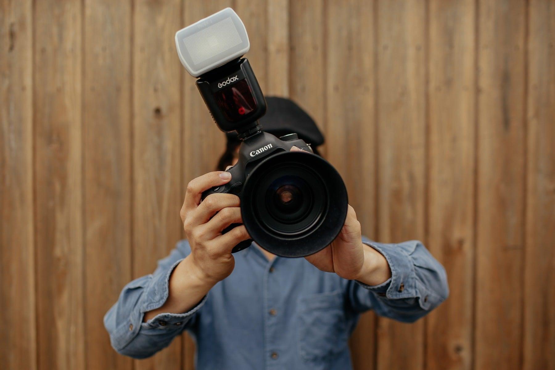 Man using Godox flash on a Canon camera