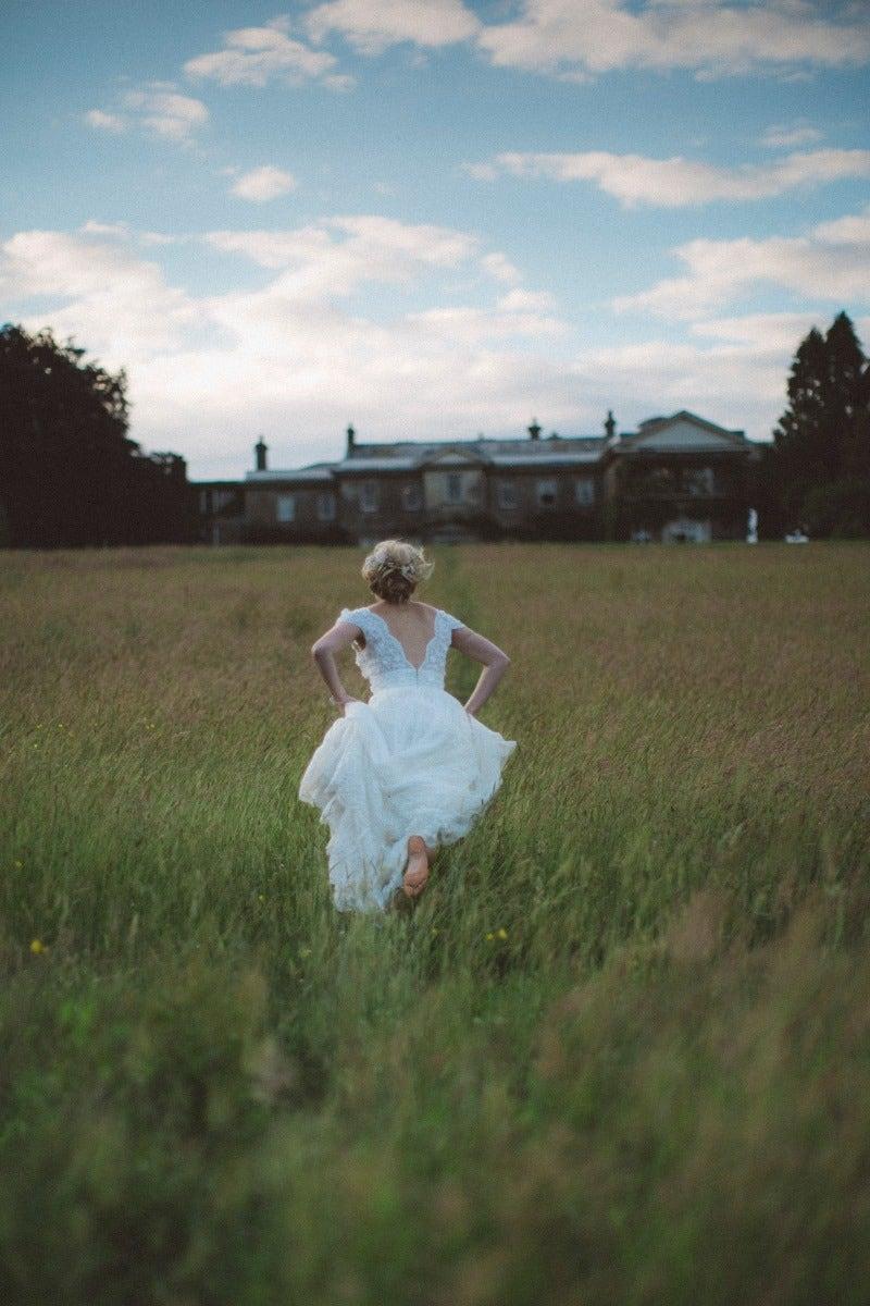 Bride running in field towards building