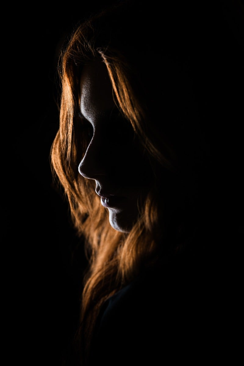 Dark portrait of woman with red hair