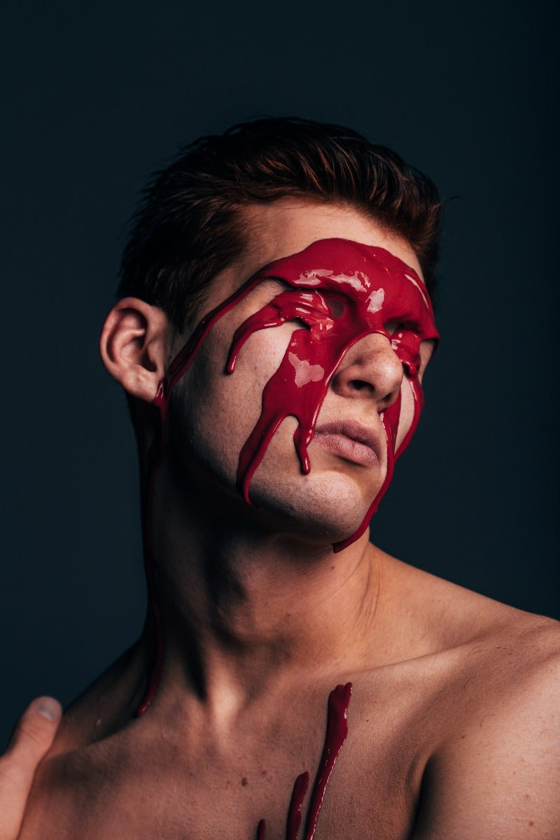 Portrait of man with red paint on face