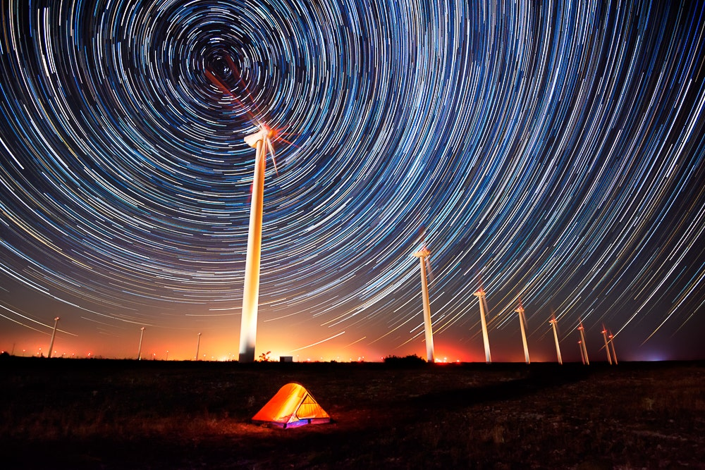 Circular star trails with windmills and tent