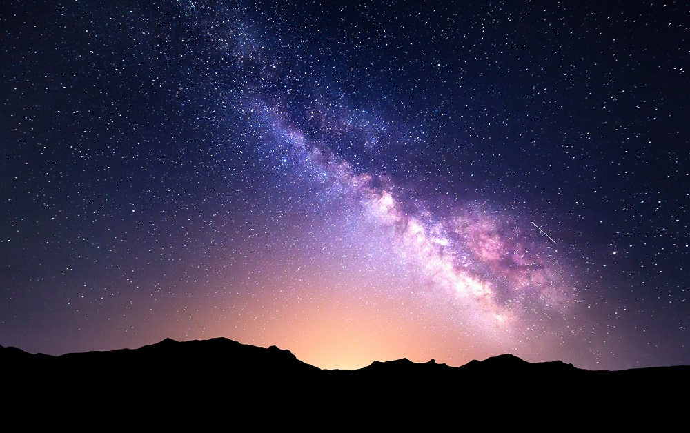 Milky Way over mountains with glow