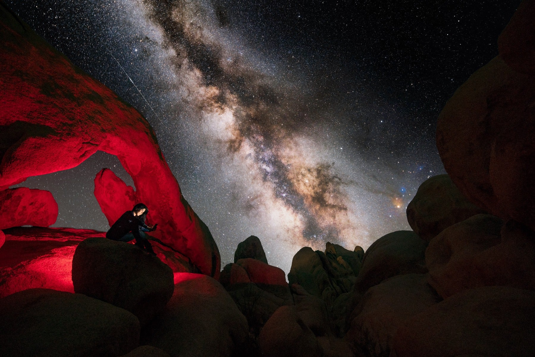 Woman under rock formation with Milky Way in background
