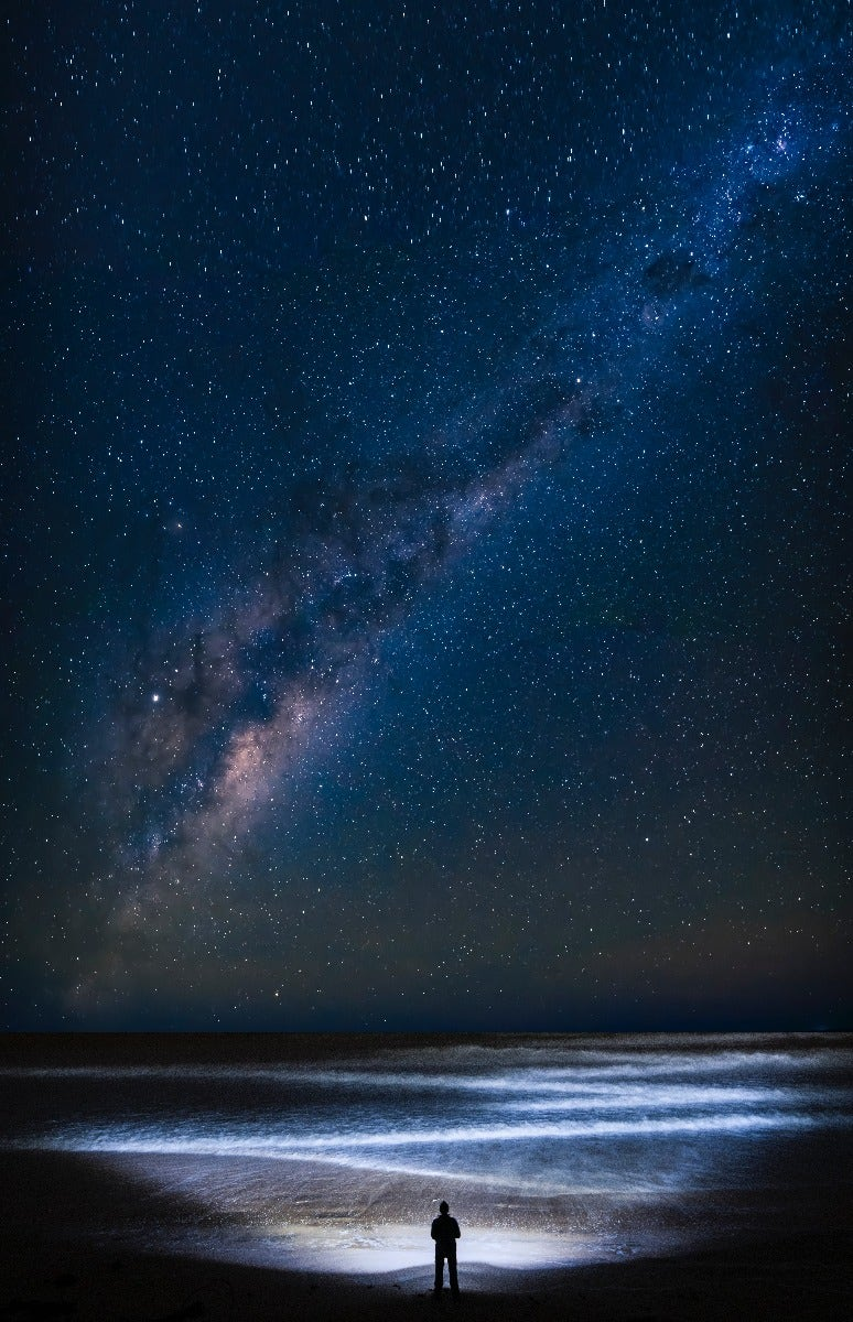 The Milky Way over person on the beach and waves