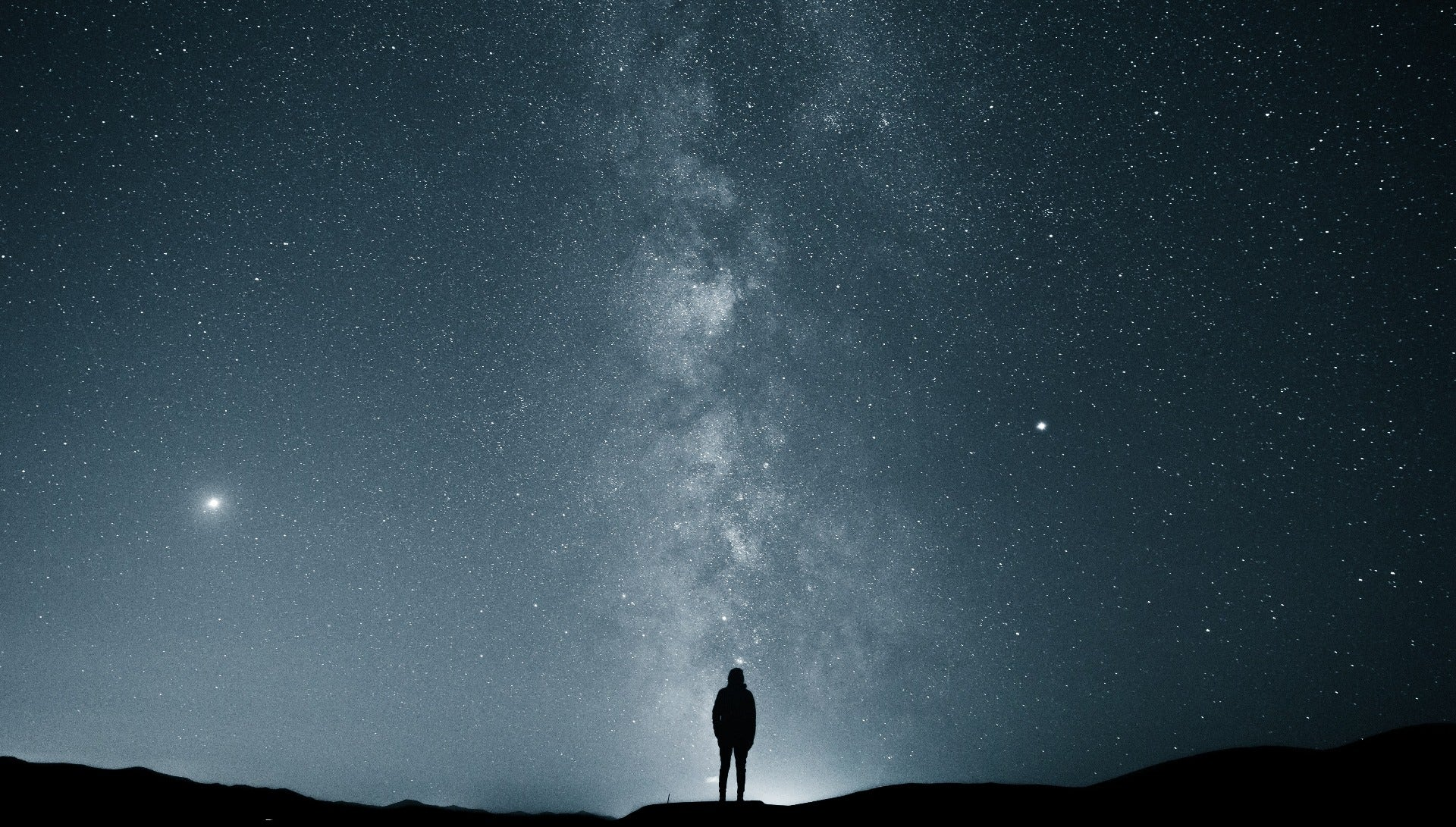 Silhouette of man in front of Milky Way galaxy