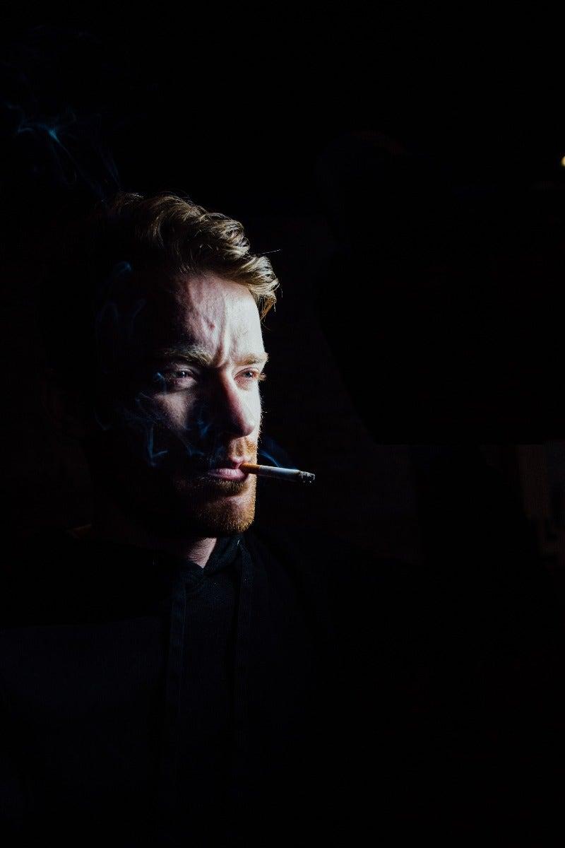 Man smoking cigarette with dark lighting